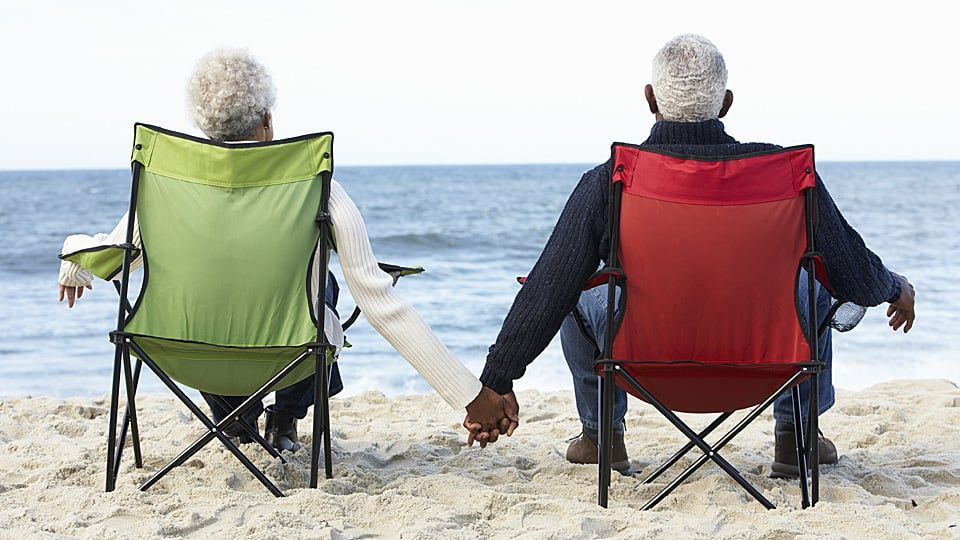 an old couple sitting on the beach holding hands