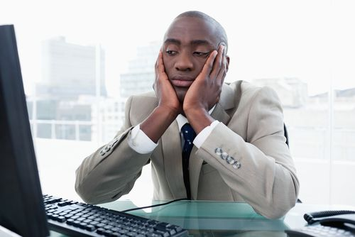 a person sitting in front of computer feeling bored