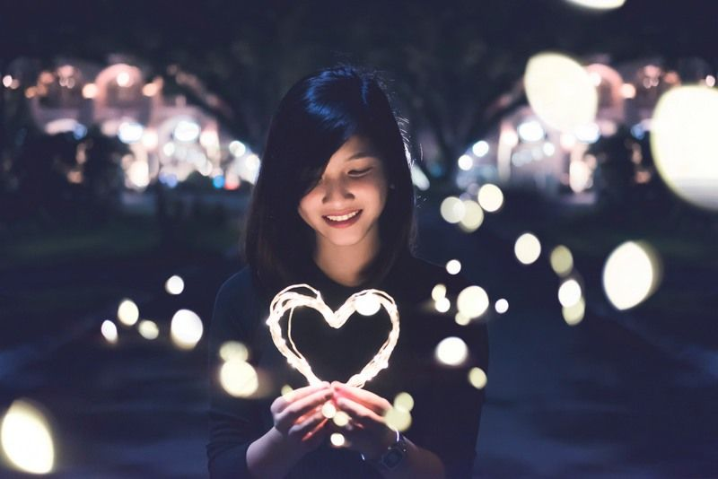 an impressed girl holding a heart shaped light