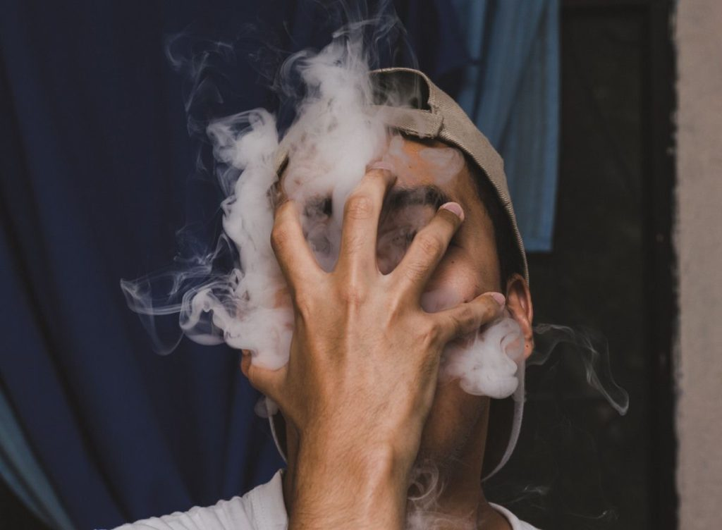 a man smoking weed with covered face showing the bad effect of drugs and credit cards.