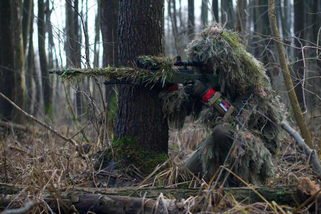 a person in camouflage holding a gun in the forest